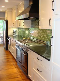 LOVE! White kitchen, cherry island, soapstone counters, hefty ORB hardware and that GREEN backsplash!