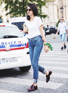 Leandra Medine in an easy white t-shirt, jeans, and oxfords, she plays up the outfit with a wrist scarf