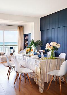 Comedor abierto al salón con pared revestida de lamas de madera en azul intenso_ 00407821