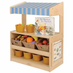 """12 months & up. Toddlers will love role playing social situations at the well designed Toddler Marketplace. This marketplace has beautifully angled shelves to hold bins and display products as well as a flat storage shelf below for additional items. The counter is perfectly sized for toddlers at 18"""" and the striped awning adds to the appeal. The clear display window has signs for a pet shop, farmers market, grocery store, and puppet theater. Bins and toys are not included. Measures 36""""H x…"""