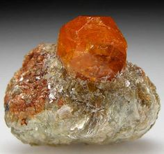 Spessartine from Nani, Loliondo, Arusha Region, Tanzania Complete orange Spessartine crystal, 13mm wide, set in bright, silvery green mica. Garnet has sharp crystal faces with no black inclusions and bright citrus orange color. Size 2.7 x 2.4 x 1.5 cm.
