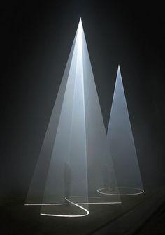Man under round slits of light in dark space