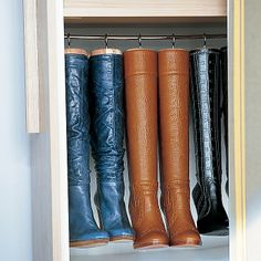 Made for Hanging: Homemade hangers preserve the shape of tall boots and maximize space. They're created by replacing the knobs on cedar boot trees with large cup hooks, which are screwed into the tops. The trees and boots then hang from a cafe-curtain rod.  From Martha Stewart