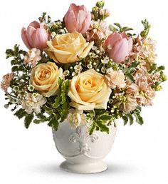 Peaches and Dreams  Pretty in peach roses, tulips, miniature carnations and stock along with white waxflower and fresh spring greens are beautifully arranged in a ceramic French country container.