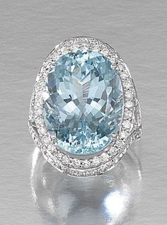 AQUAMARINE AND DIAMOND DRESS RING.  Centring on an oval aquamarine stated to weigh 20.08 carats, encased within a border of brilliant-cut diamonds, to similarly set split shoulders, size K, British hallmarks for London, 2007.