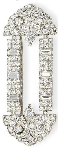 AN ART DECO DIAMOND BROOCH, BY CARTIER   The circular-cut diamond openwork plaque with shield-shaped terminals, each accented by pierced scrolling motifs and a pear-shaped diamond collet, to the baguette-cut diamond accents, mounted in platinum, circa 1925, 6.8 cm long  Signed Cartier, no. 2328