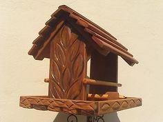 Alimentador de pássaros feito em madeira com acabamento em verniz e detalhes entalhados . Possui poleiros laterais e caixa de alimentação com capacidade para 3 xícaras de chá de sementes ou fruta. Com espaço para colocar bebedouro, barra de cereais e alimento para beija-flor. R$70,00