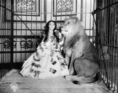 1897-Lady lion tamer caged with lion.