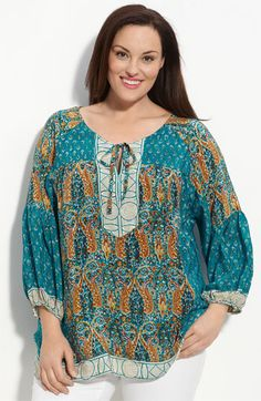 Contrasting prints color a billowy silk top styled with a drawstring tie at the keyhole neckline - plus size