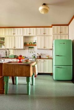 The kitchen was built around the butcher-block on legs, an old family piece. The easy-to-clean Marmoleum sheet flooring ties it to the mint-green, 1950s-style Northstar refrigerator by Elmira Stove Works.