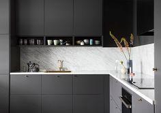 Ett sobert grått kök i den härliga kulören peppargrått med en tanke om att bli hemmets naturliga samlingsplats för hela familjen. I detta kök ser vi en slät, lät avrundad Bistro lucka och bänkskiva samt stänkskydd i klassisk Carrara marmor. Diskho och blandare i lyxig mässing blir tillsammans med knoppar i samma metall kökets smycke.