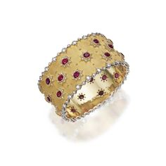 18 KARAT TWO-COLOR GOLD, RUBY AND DIAMOND BANGLE-BRACELET, BUCCELLATI, ITALY The wide hinged bangle set with oval rubies within star motifs, accented by round diamonds weighing approximately 5.15 carats, mounted in white and yellow gold, internal circumference 7¼ inches, signed Buccellati, Italy.