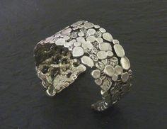 Ce bracelet manchette fabriqué en étain est disponible en argenté et en doré. Le travail de martelage en surface, sa forme asymétrique et sa finition