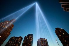 The Tribute in Light shines as One World Trade Center rises under construction