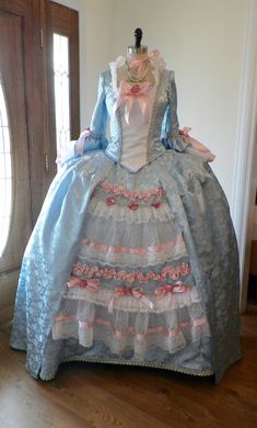 Custom made to your measurements will be this brocade Marie Antoinette dress. Dress is made from a very rich looking blue brocade with golden Rococo embellishments around the neckline and sleeves, and underskirt petticoat. This listing is for the bodice corset , the overskirt, the underskirt and the panniers cage frame...4 separate peices. Dress in the pictures shown in the blue. Dress gown costume can be constructed in blue, candy pink, or ivory, and many other colors.  I have custom…