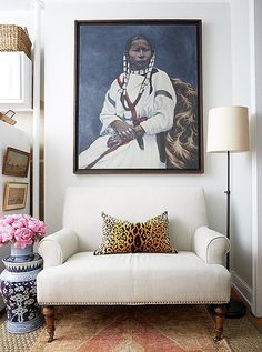 A flea market painting fits perfectly above a new linen love seat flanked by an iron floor lamp and Chinoiserie-inspired garden stool.