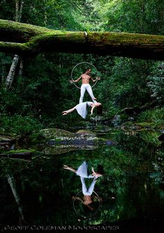"""Float. Photographer says, """"2nd in the series with Emma Goh and Steven Watson, a couple of brilliant aerialists that I shot recently in a rainforest close to where I live. Yes she is actually just lying across his feet suspended in mid air. These two were just so graceful. I was thrilled that I could get the reflection as well--fortuitously slowly flowing creek that day."""""""