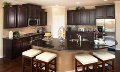 We love the dark cabinets and countertop in this @lennardallas kitchen!
