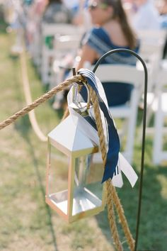 Rope, navy ribbon, and a lantern — you've got yourself a nautically beautiful aisle marker.