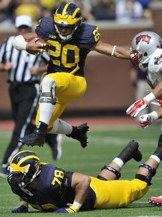 Michigan Wolverines running back Drake Johnson leaps over teammate Erik Magnuson on this fourth-quarter rush that was called back by a clipping penalty against Michigan in the fourth quarter.