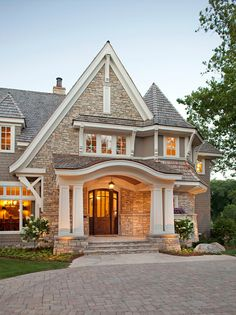 Beautiful exterior. stone exterior. dramatic roof lines. Front Entry Ideas. John Kraemer & Sons.