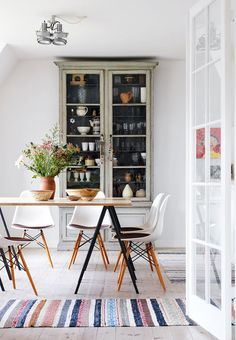 scandinavian dining room with striped rug and cabinet