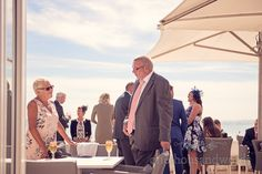 Wedding guests on sun terrace at Sandbanks Hotel Wedding. Photography by one thousand words wedding photographers