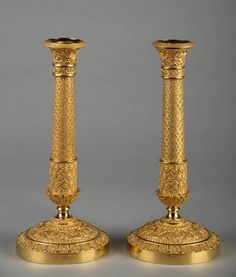 A pair of French gilt bronze candlesticks. The base is decorated with finely chiseled palmette, garlands and other floral ornaments. The stem is partly fluted and decorated with flower heads. The top part of the stem is decorated with music attributes. Circa :1830