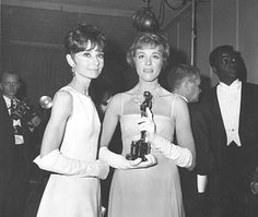 """Julie Andrews, holding her Oscar statuette, poses with Audrey Hepburn backstage at the 37th annual Academy Awards ceremony at the Santa Monica Civic Auditorium in Santa Monica, Ca., April 5, 1965. Andrews won for her role as Mary Poppins in """"Mary Poppins."""" Standing at far right is actor Sidney Poitier. (AP Photo)"""