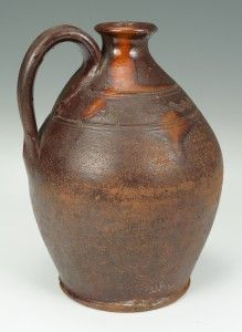 Sullivan County, Tennessee redware jug, attributed to the Cain pottery. Lead glazed jug with pulled handle, sine wave and incised lines bordering around the upper bulbous midsection, ringed collar with smoothed rim, beaded foot, bottom with areas of pooled glazing. Single thumb print to handle terminus. Provenance – Hawkes Estate located in Cooks Valley area of Sullivan County. 8″ H. 19th century.