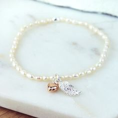 Ivory Pearl Bracelet with Wing and Heart. Can be personalized by adding letter, initials, hearts and birthstone charms. Bridal, Flower Girl by Wysh925 on Etsy https://www.etsy.com/listing/491483299/ivory-pearl-bracelet-with-wing-and-heart