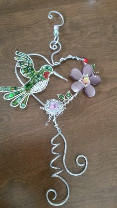 Wire wrapped beaded sun catcher with flowers and ladybugs and nest and hummingbird.