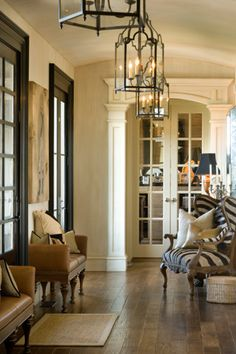 Pretty Foyer, tan leathers, wood floors, lantern chandeliers, black trim.