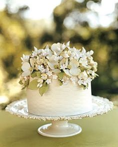 The bride ordered a cake for each table, decorated with blooms that complemented her bouquet.  Each cake was slightly different, and each was cut later to serve the guests that had enjoyed it as a centerpiece during the dinner hour.