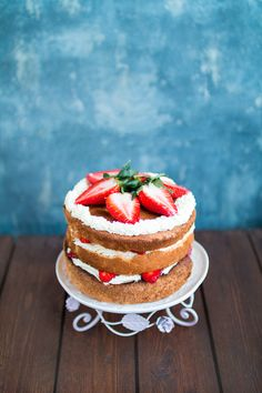 Light birthday cake for special occasion - angel food cake with fresh strawberries and mascarpone frosting. Minimalistic stalish naked  cake