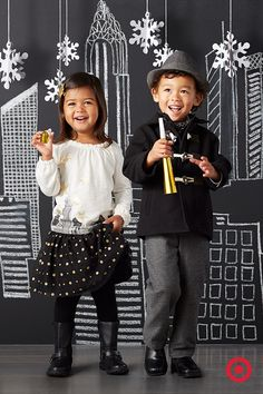 Dressed to the nines, these trendy toddlers are holiday-party ready. A gold-embellished skyline-print tee and glitter-sprinkled polka dot skirt for her. A military-style jacket, herringbone trousers and a statement-making fedora for him.