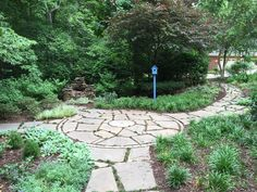 Large flagstone paths to accommodate running dogs work well in this garden.  Millstone used as focal point in paving design.
