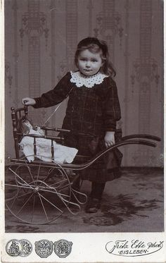 A young lady poses with her her doll and carriage, c 1900.