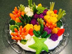 "This is a coral reef veggie tray that I created for my granddaughter's mermaid birthday party. I created the ""sand"" from two blocks of cream cheese mixed with a packet of ranch dip mix. I stood carrots and snap peas on end and then cut celery several times lengthwise to make celery fans. Small sweet peppers became rocks and smooth coral. Broccoli and several colors of cauliflower became coral. This was easy and fun to make and a real hit at the party."