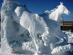 snow sculpture of horses running in water
