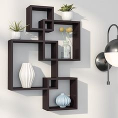 Imbue a sparse wall with visual intrigue, or add to an understated gallery display with this geometric cube shelf. Made from a mixture of MDF and solid hardwoods, this intricate design includes four intersecting square cubbies stacked in varying sizes. The asymmetrical nature of the design inspires visual interest, while creating several tiers of shelves on which to display glossy geometric vases or framed family photos. To create a soothing ensemble in your living room, start by rolling out…