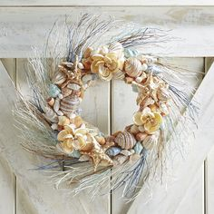 Bring home the beach vibe—without all the sand and salt. Our handcrafted wreath boasts a radial design of sunbleached twigs and natural shells, dressed to the nines with faux jewels.
