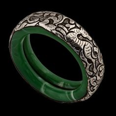 Reminiscent of jade and offsetting the silver craftsmanship adorning it perfectly, the cool smooth glass bangles and their intricate decoration are guaranteed to attract the eye, From Katmandu, Nepal ...