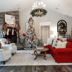 How festive and bright is this Living room all ready for the holiday season? Bright red couch cover, red themed flocked Christmas tree, mantle decor with stockings and greenery around the rustic farmhouse chandelier. #farmhousechristmasdecor #farmhousechristmasdecor #farmhousechristmastree #farmhousechristmaslivingroom #christmasstockings #christmasmantel #christmaspillows #christmasgreenery #christmasdecorationsrustic #holidaydecorating