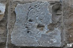 Il volto di uno scocciatore o di un condannato alla gogna scolpito da Michelangelo su un muro di Palazzo Vecchio, a sinistra della rampa d'accesso dietro la statua di Ercole e Caco