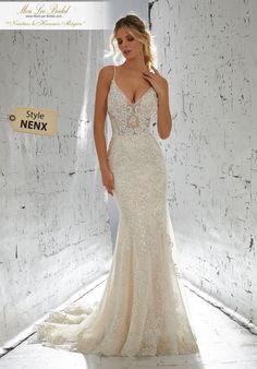 Estilo NENX Laurette Wedding Dress Sexy Yet Sophisticated, This Sheath Net Wedding Dress is Accented with Frosted Pearls and Beaded, Metallic Lace Appliqués. A Plunging V-Back and Scalloped Hemline Complete the Look. Matching Satin Bodice Lining Included. Available in Three Lengths: 55″, 58″, 61″ Colors: White, Ivory, Ivory/Champagne