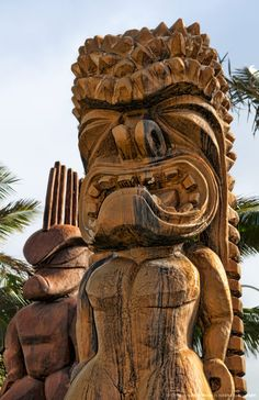 Hawaii, Oahu, Large wooden tiki statues greet visitors outside of the Polynesian Cultural Center entrance.