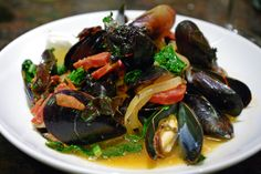 Steamed mussels with chorizo in a spicy white wine, thyme, winter greens and fresh tomato broth.