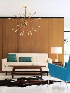 Mid century retro vintage living room with sputnik pendant light lamp and teak furniture cow hide