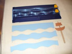 Items for making Jesus Calms the Storm craft. Cut construction paper with wavy trimmer. Crimper not shown. Glue gun the paper ship to stick. Heavier paper or laminated paper for ship would be better (sturdier).
